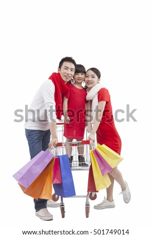 Portrait of daughter standing in shopping cart,with parents holding shopping bags
