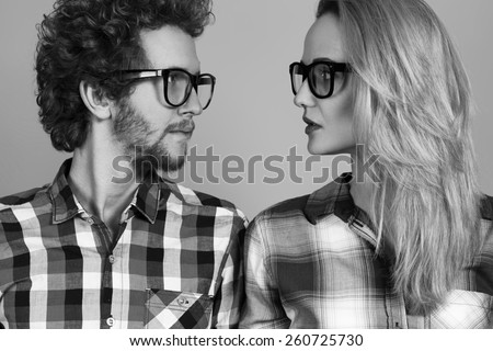 Portrait of gorgeous blond fashion man and woman in casual shirt, wearing trendy glasses posing on blue background. Perfect skin and hairdo. Vogue style. Close up. Studio shot.