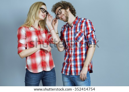 Portrait of gorgeous blond fashion man and woman in casual shirt, wearing trendy glasses posing on blue background. Perfect skin and hairdo. Vogue style. Close up. Studio shot.  - stock photo