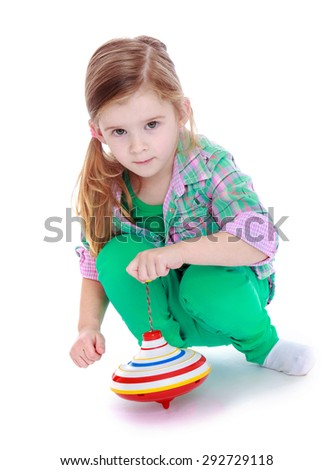 Portrait of little adorable girl blonde which spins the dreidel - isolated on white background - stock photo