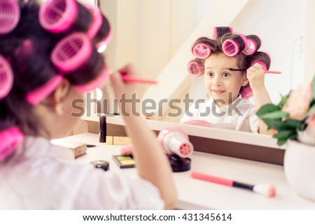 Portrait of little pretty laughing girl with pink hair curlers on her head , sitting on a chair in the dressing room and make yourself a makeover. He holds in his hand brush for applying makeup - stock photo