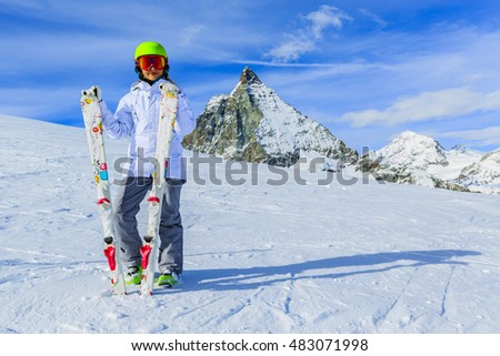 Portrait of pretty skier young girl looking far away, wearing googles  and holding in hands ski equipment, active lifestyle in Swiss Alps, Matterhorn in background.