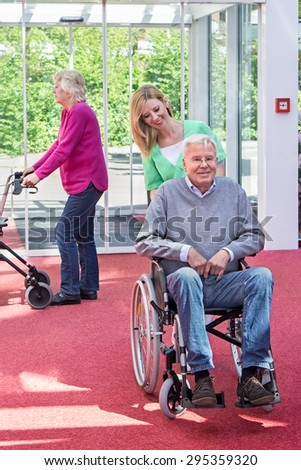 Portrait of Smiling Blond Nurse Pushing Senior Man in Wheelchair Through Lobby of Retirement Building with Woman in Background Passing By with Walker. - stock photo