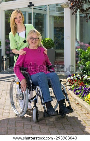 Portrait of Smiling Blond Nurse Standing Behind Senior Woman in Wheelchair Outdoors in front of Building on Sunny Day. - stock photo