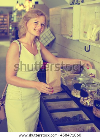 Portrait of smiling woman buying various nuts by weight in grocery shop - stock photo