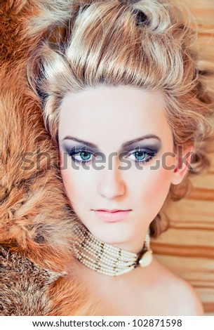 Portrait of the attractive blond woman with fur - stock photo