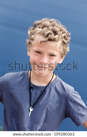 Portrait of the curly boy with a key on a neck