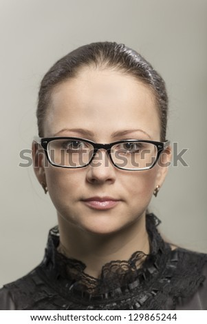 Portrait of the serious young woman in glasses - stock photo