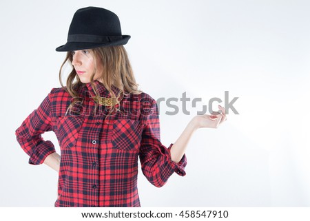 Portrait Of Trendy Young Girl In Red Plaid Shirt And Black Hat Posing With Outstretched Hand And Looking To The Side, Half-Length Studio Shot Over White Background - stock photo