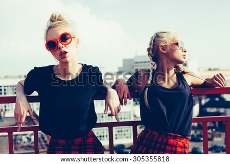 portrait of two pretty hipster blonde sisters  wearing plaid skirt and  black T-shirt. Girls smile, have fun against  urban city. - stock photo