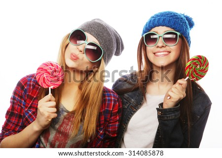 portrait of two young pretty hipster girls wearing  hats and sunglasses holding candys. Studio portrait of two cheerful best friends having fun and making funny faces. - stock photo