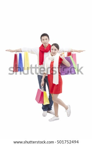 Portrait of wife holding shopping bags over shoulder,husband holding bags,opening arm