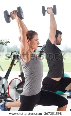 Portrait of woman and man lifting barbells during a gym workout at fitness center.