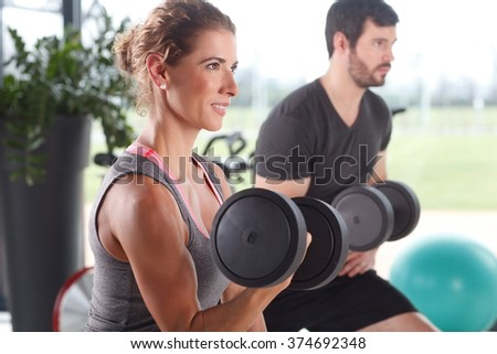 Portrait of woman and man lifting barbells during a gym workout at fitness center.  - stock photo