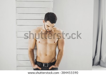 Portrait of young attractive man with muscular strong black beard, piercing sexy look in the studio posing