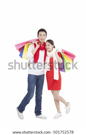 Portrait of young couple holding shopping bags over shoulders