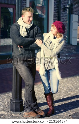 Portrait of young sensual couple in cold winter weather. Love and kiss. Young people. Snow lovers kiss city. Fashion clothing