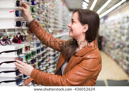 Portrait of young smiling woman in leather jacket  shopping in optical store 