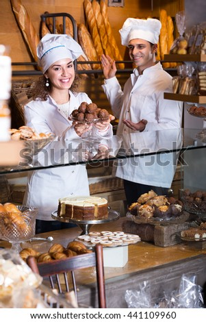 positive cooks selling tarts and sweet pastry in coffee-house - stock photo