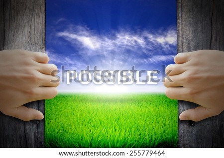 """Possible"" Motivational quotes. Hands opening a wooden door then found a texts floating among new world as green grass field, Blue sky and the Sunrise. - stock photo"