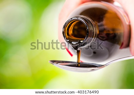 pouring a liquid on a spoon. Natural green background. Pharmacy and healthy background. Medicine. Cough and cold drug.  - stock photo