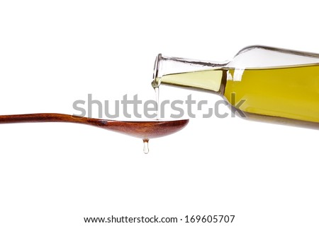 pouring olive oil on wood spoon from glass bottle against isolated on white background