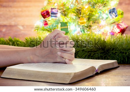 Praying hands of a women on holy bibles upon wooden table with decorative Christmas tree  and wooden background, praying to God on Christmas season
