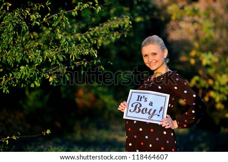 "pregnant woman  holding a sign which says ""its a boy!"""