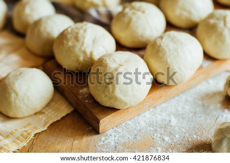 Preparing buns bread. Rustic style. Ingredients for homemade bread on wooden background. Bread cooking process.  kneading dough on wooden plate,bun cooking