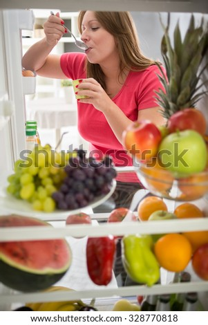 Pretty female sweetens with fresh fruit yogurt from refrigerator