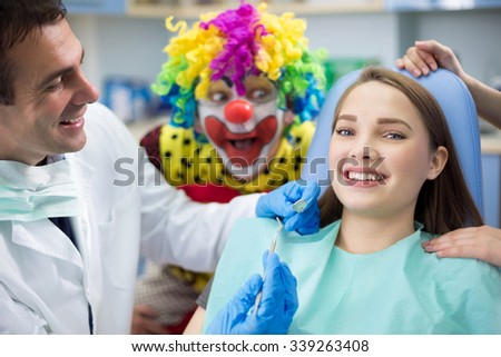 Pretty girl in dental clinic with dentist and silly clown in background - stock photo