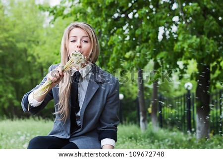 Pretty girl with dandelions in the hands - stock photo