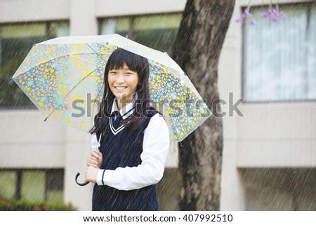 pretty  student girl holding umbrella  in the rain - stock photo