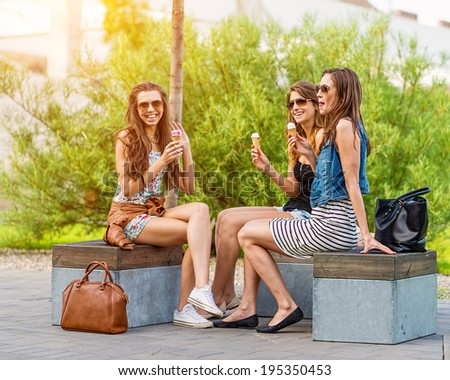 3 pretty woman eating ice cream in town, sitting on a bench, laughing