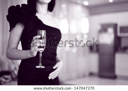 pretty  woman in glad rags,  holding a glass of champagne. interior background - stock photo