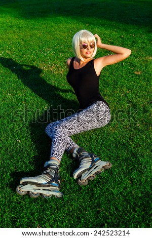Pretty young girl  in with wig  and sunglasses wearing roller skates sitting on grass in the park and enjoying spring , - stock photo