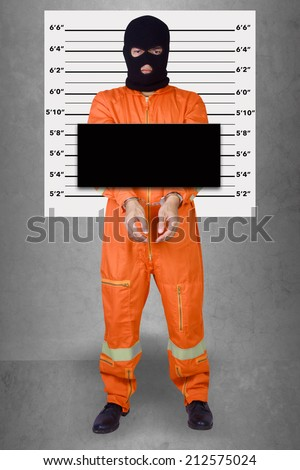 Prisoner with handcuffs standing wearing a balaclava camouflage face in jail against gray police lineup or mug shot background - stock photo