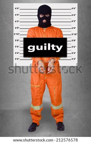 Prisoner with handcuffs standing wearing a balaclava camouflage face in jail against gray police lineup or mug shot word guilty - stock photo