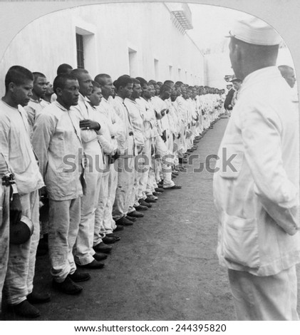 500 prisoners in formation against a wall, under guard, at the San Juan, Puerto Rico Jail 1900, shortly after the U.S. annexation of the former Spanish possession following the Spanish American war. - stock photo