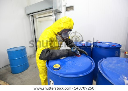 Professional in uniform filling barrels with chemicals - stock photo
