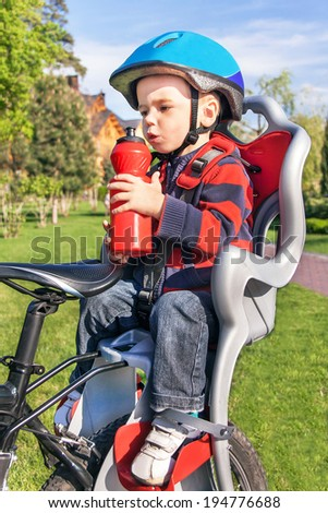 Protection on the bicycle. Baby boy is in the bicycle chair (seat) with a biking helmet on  head and bottle of water in hands during bicycle ride. Child has trip in the summer day. Travel concept.