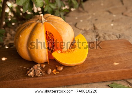 Pumpkin lies on a wooden board, next to green leaves, nuts, seeds, spices and pumpkin slice.Preparation for Halloween party