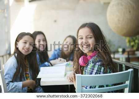 pupils at desk in elementary school - stock photo
