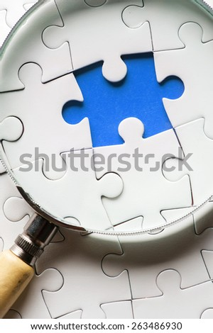 -Puzzle pieces with a magnifying glass. Concept image of detecting a defect. - stock photo