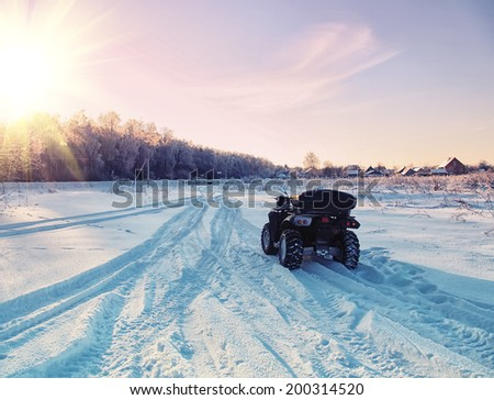 quad bike on a winter road in a field at sunset. focus on quad bike.  - stock photo