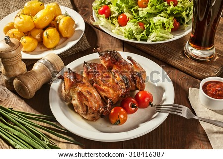 quail with tomatoes, potatoes, salads and beer