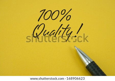 100% Quality note with pen on yellow background