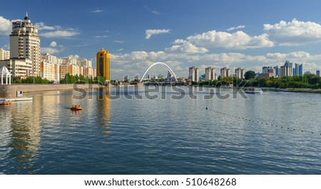 "Quay of the river Ishim in Astana. Bridge ""Karaotkel"" (Ramstore). /Astana, Kazakhstan - September 1, 2013: People ride on pleasure boats and catamarans."