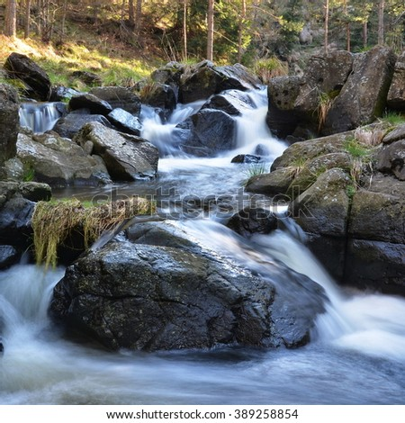 Quick mountain stream and large wall - stock photo