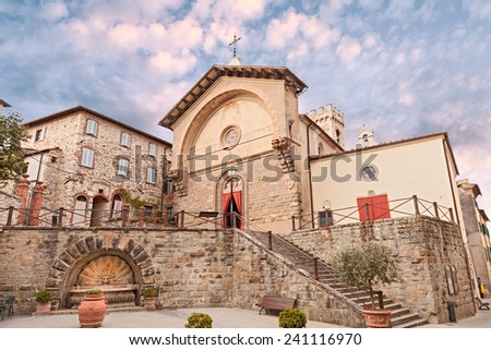 Radda in Chianti, Siena, Tuscany, Italy: the church Propositura di San Niccolo', the main catholic place of worship, at the bottom the fountain with lion head  - stock photo